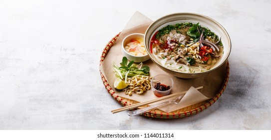 Pho Bo vietnamese Soup with beef in tray on wooden background copy space