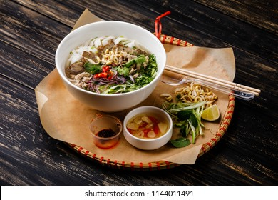 Pho Bo vietnamese Soup with beef in tray on wooden background