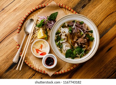 Pho Bo vietnamese Soup with beef on wooden background