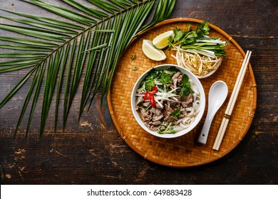 Pho Bo vietnamese Soup with beef on bamboo tray and palm branch on wooden background