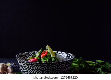 Pho Bo vietnamese soup with noodles, beef, chili pepper, onion,  cilantro and lime on dark black background with copy space on top