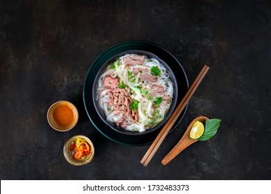 Pho Vietnam sur la table de la cuisine sombre. La nouille de boeuf ou le Pho Bo est le boeuf, la nouille de riz, l'herbe dans un délicieux bouillon. Servir avec du chili, de la sauce au chili, de la chaux. Meilleur street food du Vietnam
