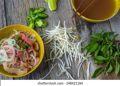 Pho Vietnamese beef soup on a wooden background