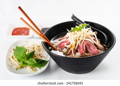 Pho - Vietnamese Rare Beef noodle soup on white background with Hoisin Sauce, Hot sauce, spices, beansprouts, and fresh basil