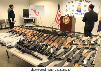 Phoenix, Ariz. / US - January 25, 2011: Reporters review guns on display during an announcement about arrests and weapons seizures made during Operation Fast and Furious. 3969