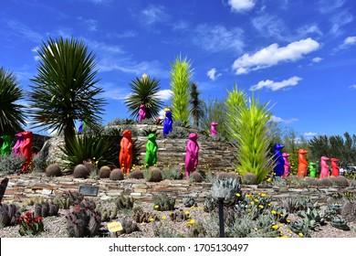 Phoenix, AZ/USA-March 20, 2020--A beautiful desert landscape and artwork at the entrance to the Desert Botanical Gardens under a deep blue sky.