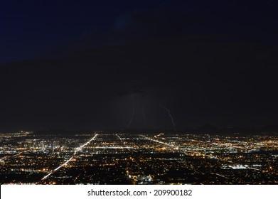 Phoenix city lights at dusk with three lightning strikes