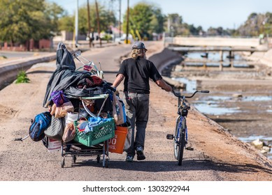 Phoenix, USA - January 19, 2019: A homeless man pulls an overladen shopping cart along a path next to the Arizona Canal. At the time of the photo the canal was drained for cleaning.