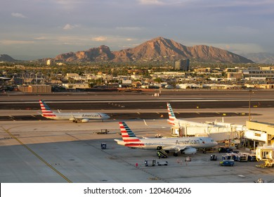Phoenix,Az/USA - 10.14.18 - Phoenix Sky Harbor International, Airport American Airlines aircraft parked at gates at the Phoenix International Airport prior to take-off, Camelback Mountain glows.