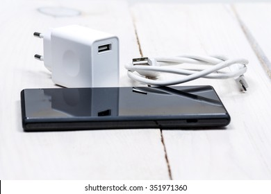 Phone accessories, usb cables, headphones on a white wood background