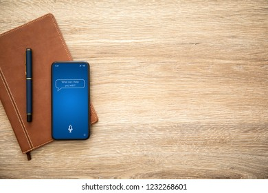 phone with app personal assistant on screen and wooden table with a notebook