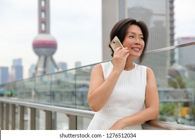 Phone Asian woman mature middle age chinese businesswoman talking business on mobile smartphone call outside on Shanghai street with Pearl tower in background. China travel.a