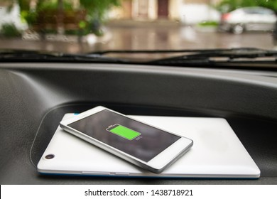 Phone battery wireless charge sharing technology. Wireless charge sharing smartphone, tablet in the car in rainy weather