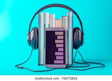 Phone with black headphones with a stack of books on a blue background. The concept of audio books and modern education