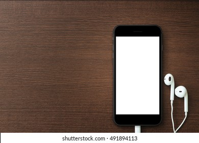 phone blank screen and headphone on wood table, mockup new smartphone style