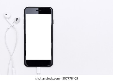 phone blank screen and headphone on white table top view