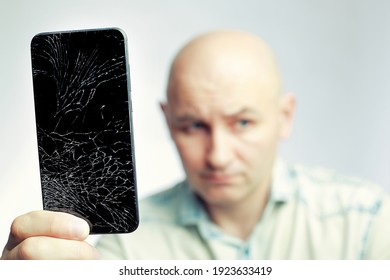 Phone With A broken screen close-up. A white man is holding a black smartphone with a cracked display. The concept of restoring and repairing gadgets