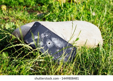 A phone with a broken touch screen and a hole from a bullet in a grass near a large stone