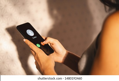 Phone call from a anonymous stalker. Stalking or bullying with phone concept. Stalker caller, scammer or stranger. Woman answering to incoming call. Ex boyfriend with fake identity.