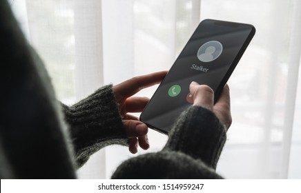 Phone call from a stalker at home. Stalking or bullying with smartphone concept. Stalker caller, scammer or stranger. Woman answering to incoming call. Ex boyfriend with fake identity.