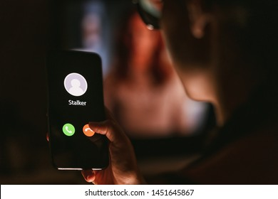 Phone call from a stalker late at night. Stalking or bullying with smartphone concept. Stalker caller, scammer or stranger. Woman answering to incoming call. Ex boyfriend with fake identity.