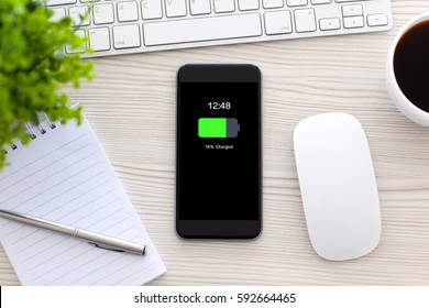 phone with charged battery screen on table in office
