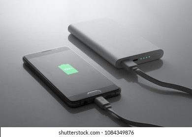 the phone is charged from the powerbank, in dark tones, 100% charge