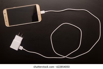 Phone with charger on black background