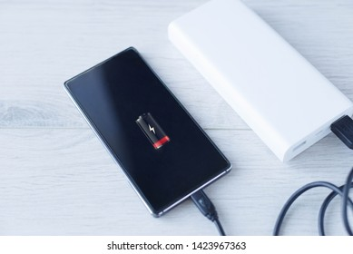 The phone is charging with Power bank. Portable Power Bank