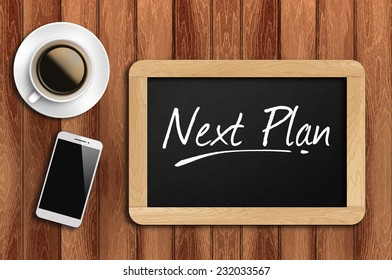 Phone, Coffee And A Chalkboard On The Wooden Table Written Next Plan.