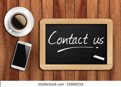 Phone, Coffee And A Chalkboard On The Wooden Table Written Contact Us.
