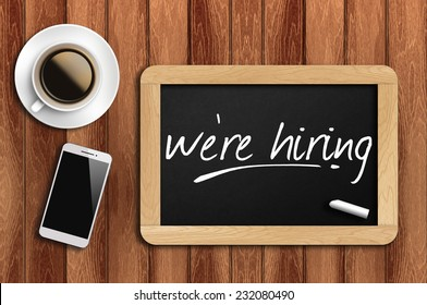 Phone, Coffee And A Chalkboard On The Wooden Table Written We Re Hiring