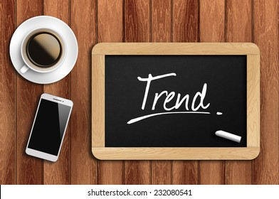 Phone, Coffee And A Chalkboard On The Wooden Table Written Trend.