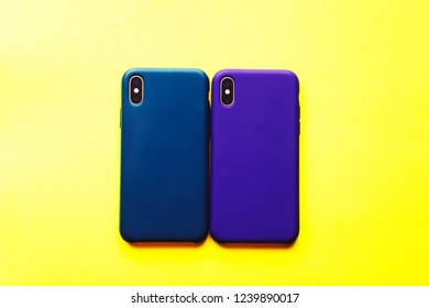 The phone is in a cover on a colored background