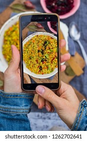 Phone food photo. Hands take smartphone food photography of Italian risotto rice or vegetables pilaf, colored pilau for social networks or blogging. Vegan, vegetarian healthy food