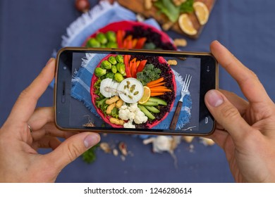 Phone food photography for social networks posts, restaurants, cafes with hands holding smartphone camera. Vegan, vegetarian lunch on table. Buddha bowl balanced plate