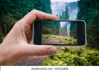 phone in hand man (photographing the landscape)