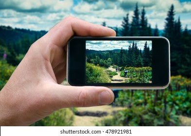 phone in hand man. photographing the landscape. photos from your phone, Self, photographing on the phone, the man photographs the mountain landscape on the phone .smartphone. side view