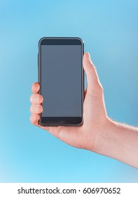 Phone in hand on blue background. Concept of mobile device theme.