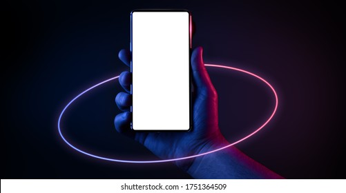 Phone in hand. Silhouette of male hand holding bezel-less smartphone with futuristic neon light circle on dark background. Screen is cut with clipping path.