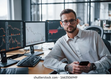 With phone in hands. Male stockbroker in formal clothes works in the office with financial market.