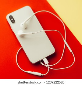 Phone and headphones on a colored background