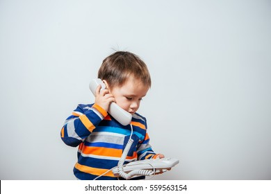 phone on the wire. child speaks on the phone wire. boy talking on a wired phone