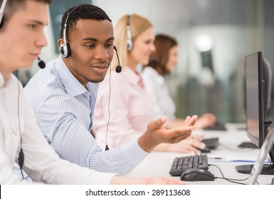 Phone operator working at call centre office helping hiss colleague.