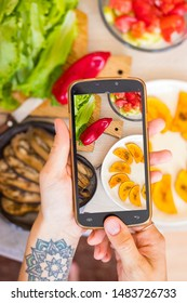 Phone photography of food in cafe. Hands take photo of baked vegetables - pumpkin, aubergine, bell pepper. Blogging style photo and social media content.