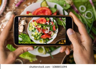 Phone photography of food. Woman hands take photo of lunch with smartphone for social media. Fresh vegetables Greek salad. Raw vegan vegetarian healthy dinner