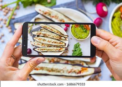 Phone picture of food. Hands make smartphone photography of eggplants for social media blogging. Concept for online order services. Vegan meal.