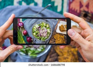 Phone picture of food. Hands make smartphone photography of vegetables detox salad for social media blogging. Concept for online order services. Vegan meal.