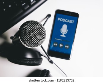 Phone with podcast livestream with microphone, headphones and keyboard on white table. Top view