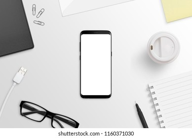 Phone with round edges on white desk. Isolated screen for app or web site presentation mockup. Flat lay. Top view.